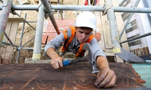 A construction worker uses a hammer to nail tiles to the wall of a new home
