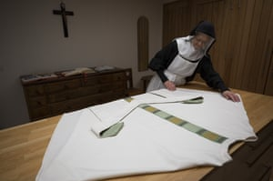 A nun prepares a priest's attire