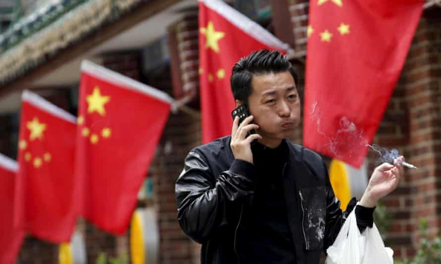 A smoker walks past Chinese national flags in front of a restaurant in Beijing.