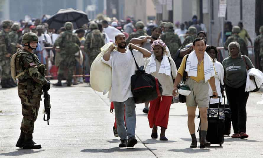 Members of the National Guard help Hurricane Katrina victims evacuate from the convention center in New Orleans on 3 September 2005.