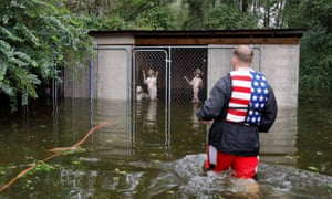A volunteer rescues panicked dogs that were left caged by an owner in North Carolina, in the wake of Florence's torrential rains.