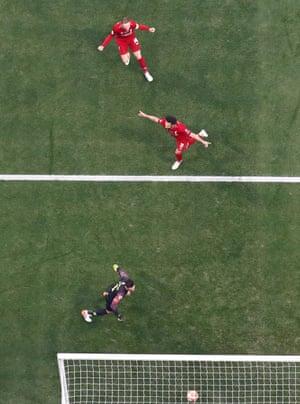 Liverpool's Mohamed Salah celebrates scoring their first goal with Jordan Henderson as Tottenham's Hugo Lloris looks dejected.