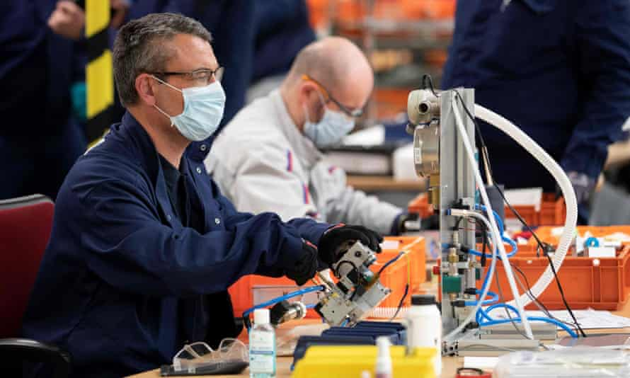 Peugeot-Citroen staff assemble parts of medical ventilators in Poissy, France.
