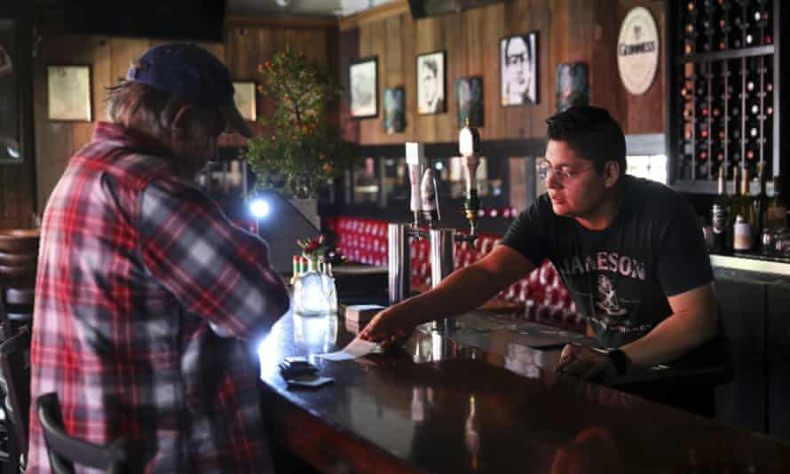Daniel Ibarra, right, gives a manually written receipt to a customer, Mark Costales, who paid for lunch in cash, at Murphy's Irish Pub & Restaurant, in Sonoma on Wednesday.