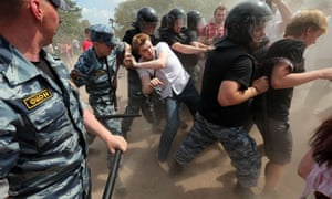 Police push a gay rights activist at a gay pride event to prevent clashes with anti-gay protesters at the Marsovo Field in St Petersburg Russia 29 June 2013.