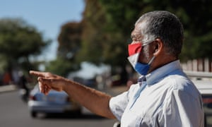 A man wears a face mask while walking on a street in Asuncion, Paraguay, 08 May 2020.