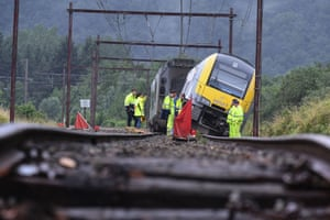 Rochefort, Belgium: Rail workers stand near a derailed carriage after heavy rains and floods hit the area.