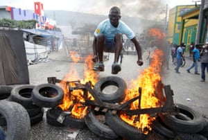 A protester hurdles a burning barricade during a protest in Port-au-Prince, the Haitian capital