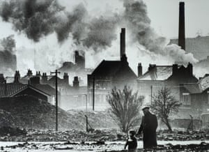 An elderly man and child walk across some wasteland. Smoke and pollution from the local factories can be seen in the background.