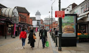 People walk past a social distancing sign in Oldham, Greater Manchester
