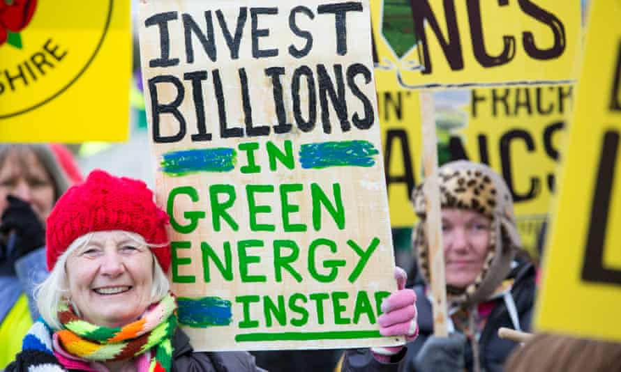 Demonstrator holds up a sign calling for more investment in green energy