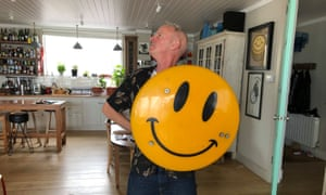 Norman Cook, or Fatboy Slim, holding a smiley face at his home in Brighton.