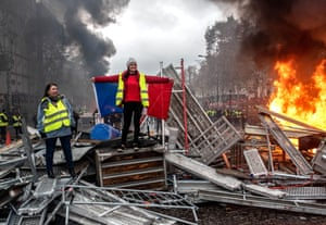 Two women stand atop the fallen barriers while flames burn behind them.