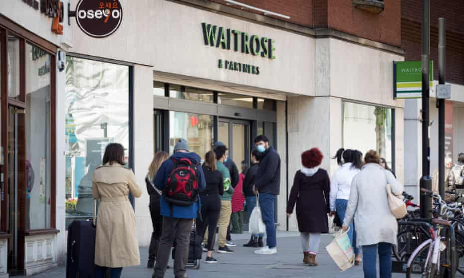 Shoppers observe physical distancing rules as they queue outside a Waitrose store in Islington, north London.