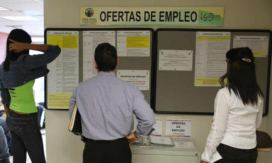 People look at the job listing posted on the wall at an unemployment office in San Juan, Puerto Rico, on Tuesday.