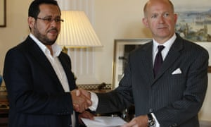 Dominick Chilcott, right, British ambassador in Turkey, hands over a letter of apology from the UK government to Libyan dissident Abdel Hakim Belhaj.
