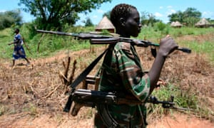 An LRA rebel passes a village on his way to the group's camp in Sudan.