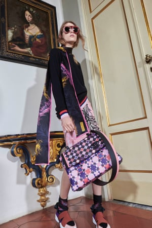 A model in 2016 wearing the 'Tagliatella' scarf and skirt featuring the 'Piume' motif. The handbag shows the 'Monreale' print.