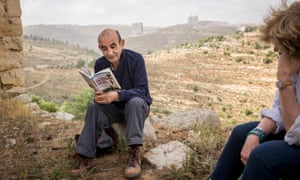 Raja Shehadeh, reading to visiting journalists from his work in the terraced hills outside Ramallah in the West Bank in 2014.