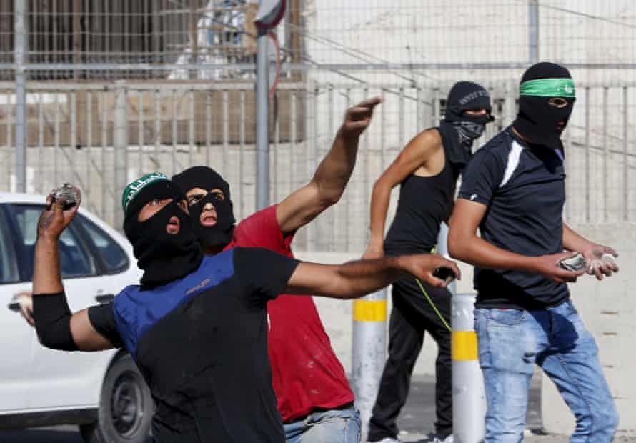 Palestinians throw stones towards Israeli border police during clashes at a checkpoint between Shuafat refugee camp and Jerusalem.