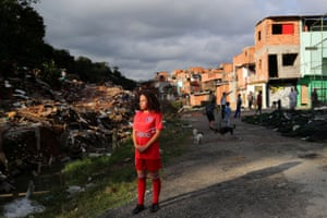Vitoria Batista Oliveira, 14, waits for a boy to fetch a missing ball during a football training session in Jardim Peri Alto slum, on the outskirts of the city.