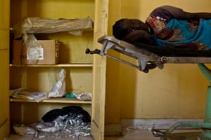 A woman lies on a delivery bed waiting to deliver next to a cupboard full of spoilt medical equipment, at a clinic in Malakal