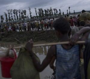 Rohingya refugees walk across paddy fields at dusk
