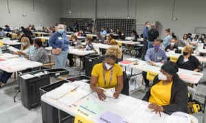 Gwinnett county election workers handle ballots as part of the recount for the 2020 presidential election.