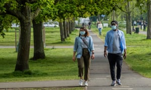 A couple walking in a park in London, both wearing face masks
