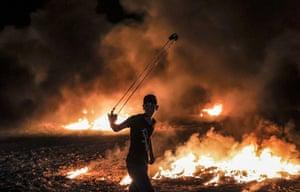 Gaza City: A Palestinian protester swings a slingshot near burning tyres
