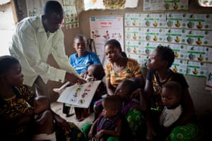 Bati Bobubela, a community health worker at a clinic in Yatutu, shows women how to prevent their children getting ill