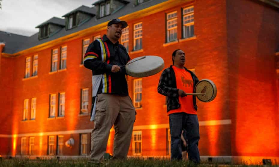 Thundersky Justin Young, left, and Daryl Laboucan drum and sing healing songs at a makeshift memorial to honor the 215 children whose remains have been discovered buried near the former Kamloops Indian Residential School in British Columbia, earlier this month.
