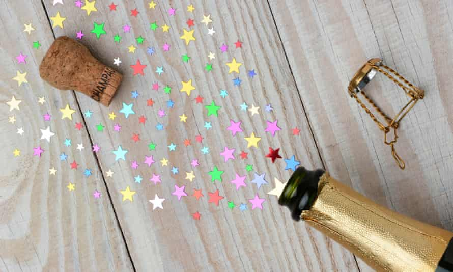 Overhead of a bottle of champagne with the cork popping on a rustic wood table. The spray from the bottle is stars of various siECWY1X Overhead of a bottle of champagne with the cork popping on a rustic wood table. The spray from the bottle is stars of various si