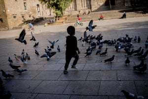A young boy runs among pigeons in Barcelona's Cathedral Square
