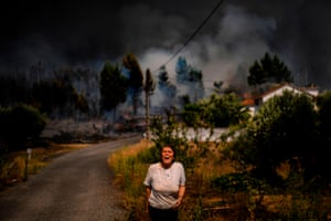 A villager shouts for help as a wildfire approaches a house in the village of Casas da Ribeira.