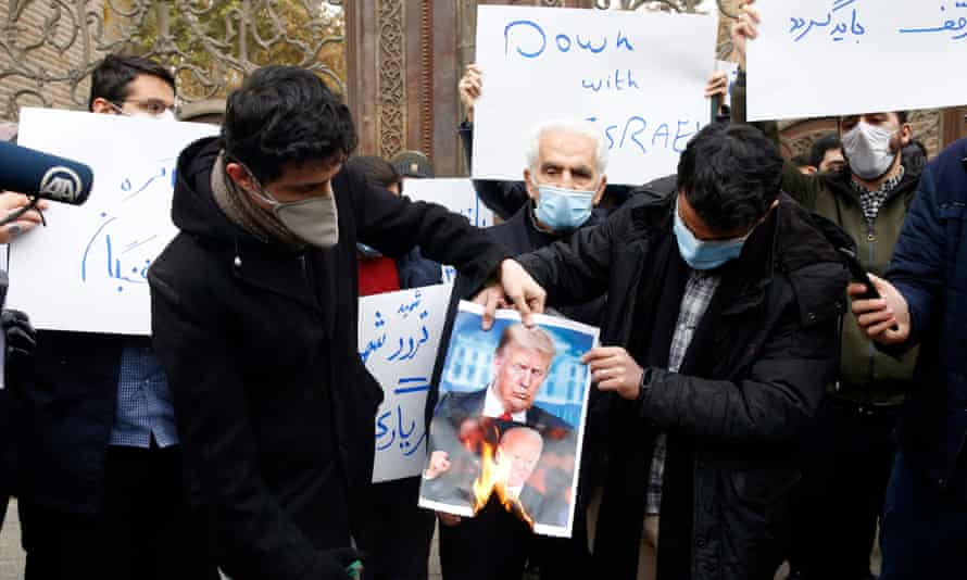 Iranian hardliners burn a picture of President Donald Trump and President-elect Joe Biden during a protest over the killing of Fakhrizadeh.
