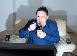 Single man eating tin of beans in front of television England UK