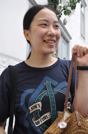 Wan Yan Qian, 30, from China, wearing a Cohen T-shirt (Ain't No Cure for Love), a united hearts badge pinned to her basket, outside Cohen's house on Hydra