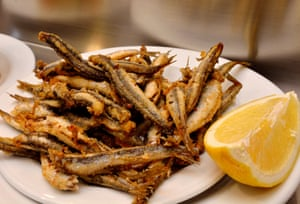 Plate of batter-coated sprats with lemon.