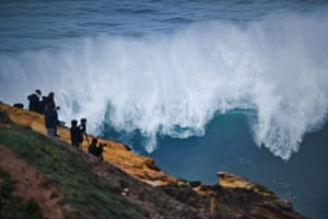 People take pictures from the cliff during a big-wave surfing session at Praia do Norte in Nazaré