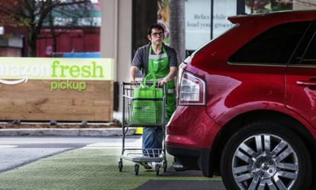 An AmazonFresh Pickup employee wheels grocery bags to a customer vehicle