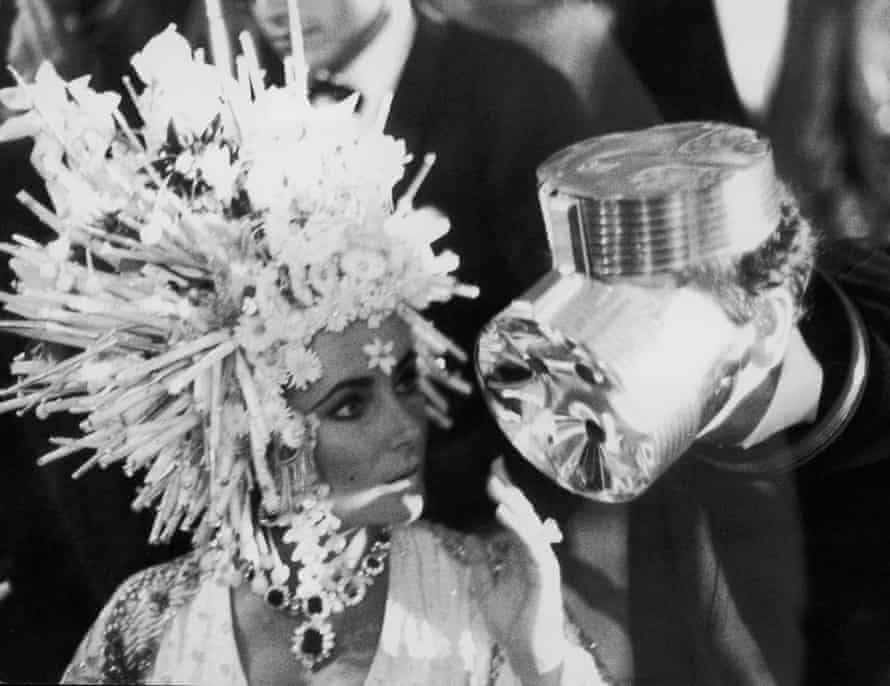 Elizabeth Taylor in a headdress of silver spikes, orchids and lilies chats to designer Cardin, who is wearing what looks like an aluminium gas mask.