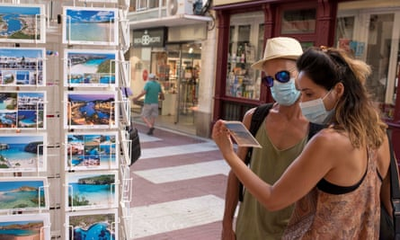 Two tourists look at a postcard at a souvenir shop in the island of Menorca, Balearic Islands.