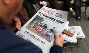 Man reads a newspaper featuring a photo of Chinese leaders attending a tree planting ceremony.