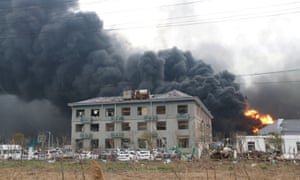 Smoke billows from fire behind a damaged building following an explosion at the pesticide plant in Yancheng.