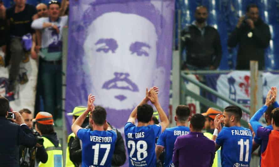 Fiorentina's players applaud the travelling fans in Rome in front of a banner of Davide Astori.