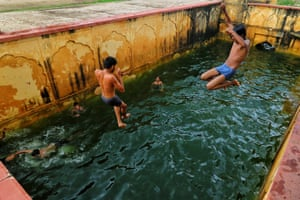 Jaipur, IndiaChildren jump into a step-well (baori) after it was filled with rain water