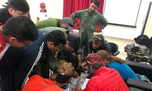 Rescued mountaineers look at an aerial picture after arriving at an Indo-Tibetan border police camp in Pithoragarh