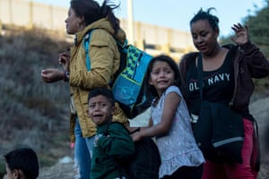 A group of Central American migrants surrender to US border patrol agents after jumping over the metal barrier separating Playas de Tijuana in Mexico from the US in 2018.