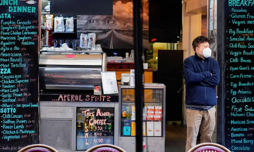 Man in mask stands in front of cafe in Melbourne